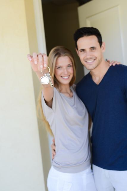 happy couple handing home keys in front of house door