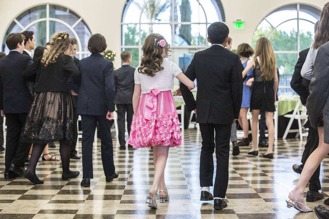 Dance partners in the 6th-8th grade class escort each other to their tables for dinning instruction during the final day of Summerlin Cotillion on Saturday, April 01, 2017,  at Vistas Community Ce ...
