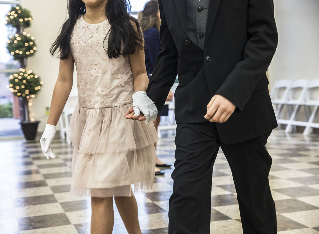 Dance partners in the 6th-8th grade class escort each other to their tables for dinning instruction during the final day of Summerlin Cotillion on Saturday, April 1, 2017,  at Vistas Community Cen ...