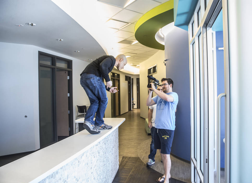 """Dr. Zubin Damania, AKA """"ZDoggMD,"""" left, dances on the front desk at Turntable Health while director Tom Hinueber  shoots footage on Wednesday, March 8, 2017, in Las Vegas. Dr. Da ..."""