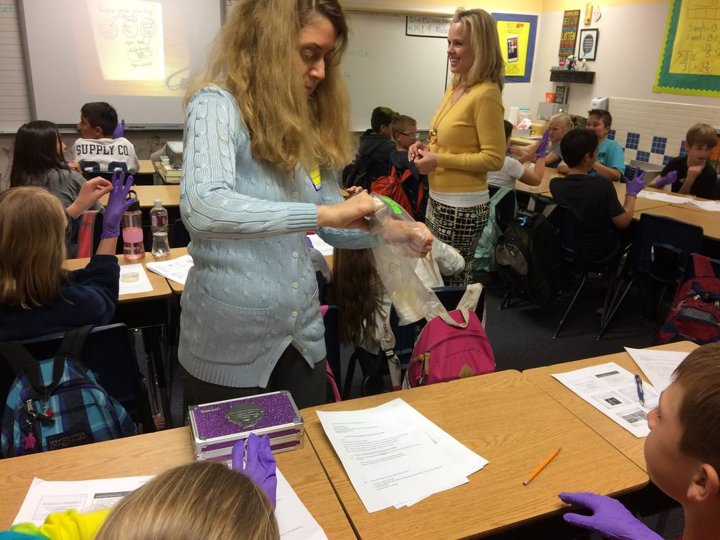 Vanessa Maniago, spokesperson for the teaching university, shows students a petri dish with e coli bacteria growing in it. The fifth graders got to do an experiment with their own petri dishes, pu ...
