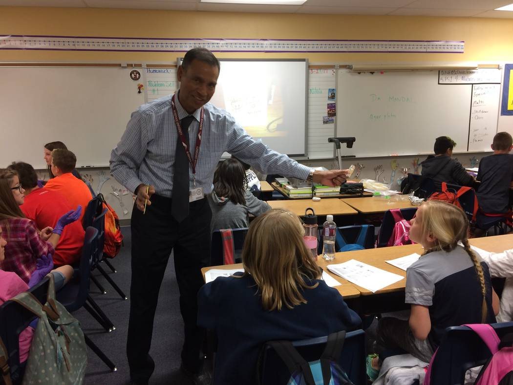 Manas Mandal, an associate professor at Roseman University, shows students a petri dish with e coli growing in it March 28, 2017 at Gooslby Elementary School. The university has begun a partnershi ...