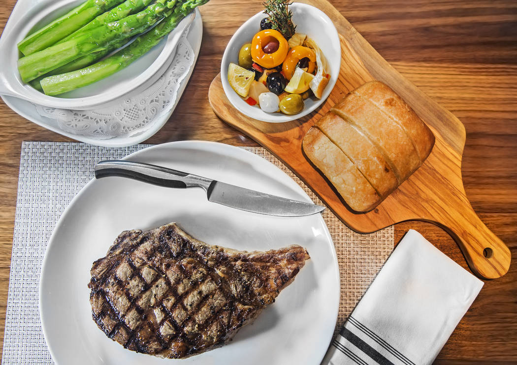The 22 oz. bone-in rib-eye steak, with buttered jumbo asparagus, bread, roasted garlic and olive garnish on Tuesday, April 26, 2017, at Redwood Steakhouse, at the California hotel-casino, in Las V ...
