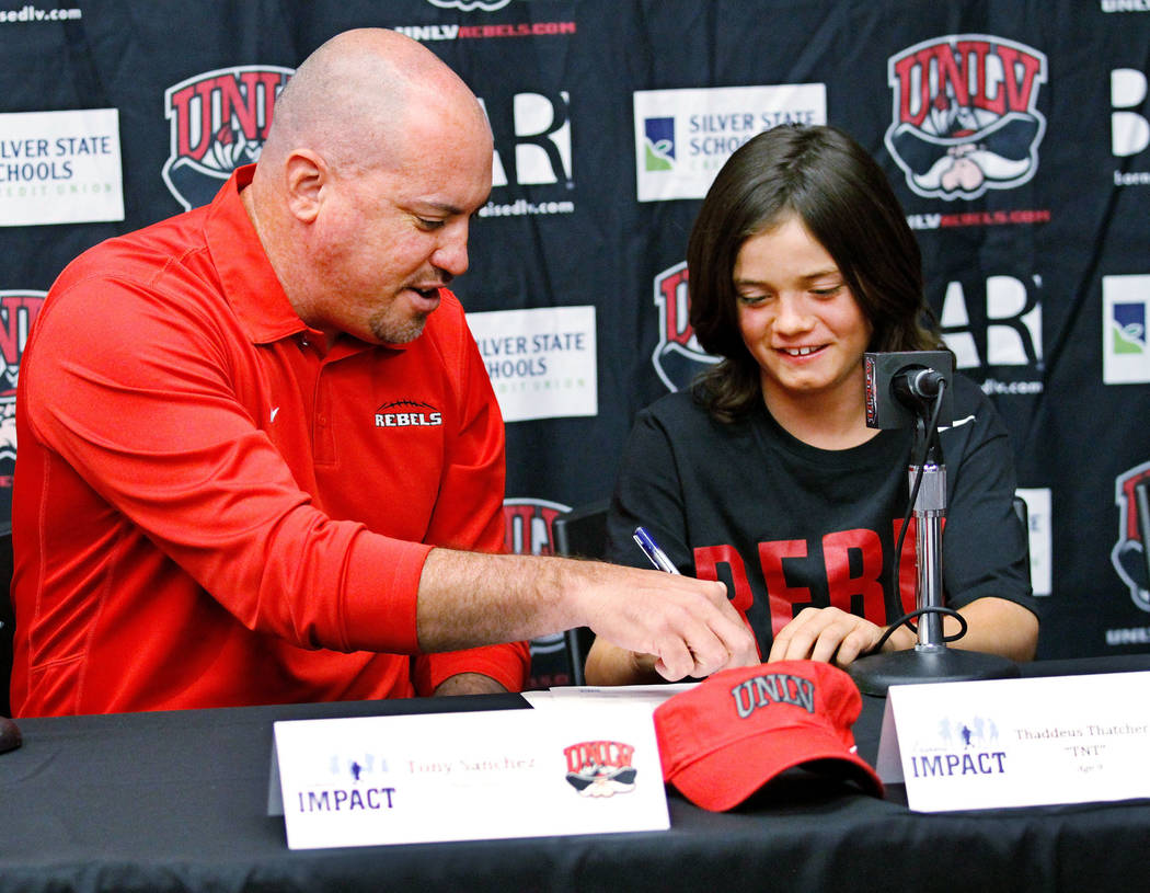 Thaddeus Thatcher, 9, who is battling cancer, signs with UNLV football coach Tony Sanchez during a news conference at UNLV in Las Vegas, Monday, May. 1, 2017.  Chitose Suzuki Las Vegas Review-Jour ...