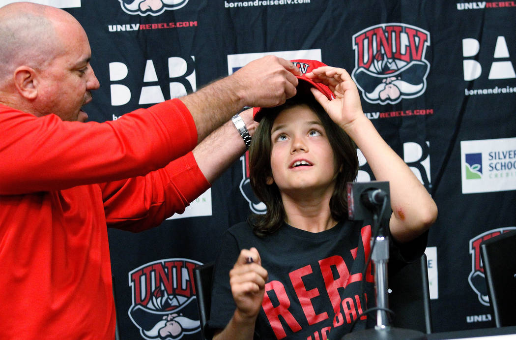 UNLV football coach Tony Sanchez helps Thaddeus Thatcher, 9, who is battling cancer, to wear a UNLV cap during a news conference at UNLV in Las Vegas, Monday, May. 1, 2017.  Chitose Suzuki Las Veg ...