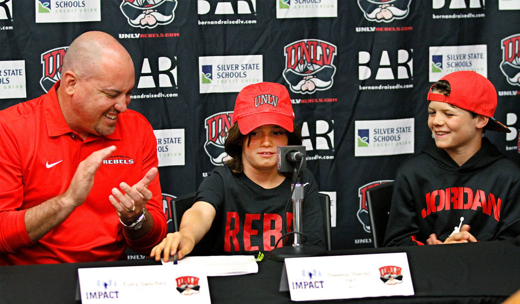 Thaddeus Thatcher, 9, center, who is battling cancer, signs during a news conference at UNLV in Las Vegas, Monday, May. 1, 2017,  as UNLV football coach Tony Sanchez, left, and Thatcher's brother  ...