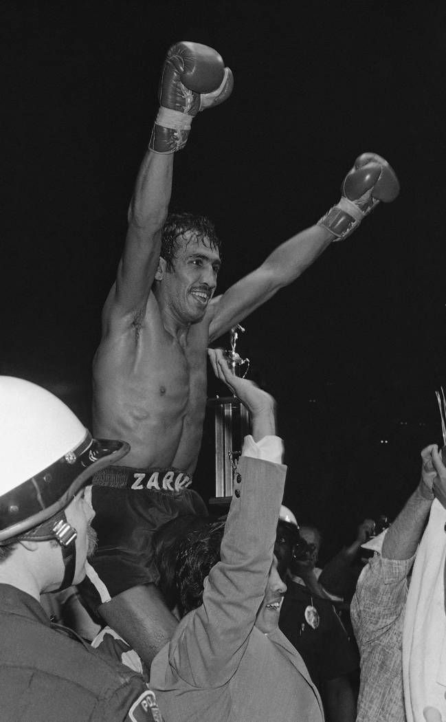 Bantamweight champion (WBC) Carlos Zarate raises arms in victory aftor knocking out the WBA champ, Alfonso Zamora, in the fourth round of a 10 round bout Saturday, April 23, 1977 in Los Angeles. I ...