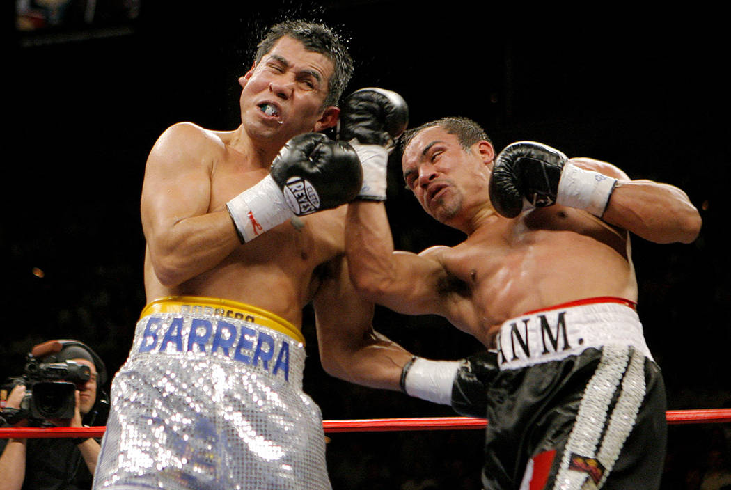 Marco Antonio Barrera, left, of Mexico, takes a punch from Juan Manuel Marquez, also of Mexico, in the sixth round of a WBC super featherweight championship boxing match on Saturday, March 17, 200 ...