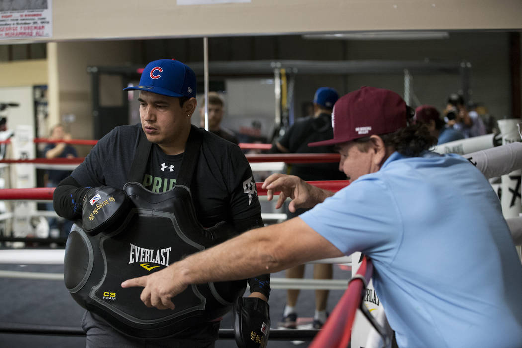 "Eddy Reynoso, left, with his father Jose ""Chepo"" Reynoso, give directions to Saul ""Canelo"" Alvarez, not pictured, during training at their gym on Wednesday, April 12, 2017, in San Diego, Calif. Al ..."