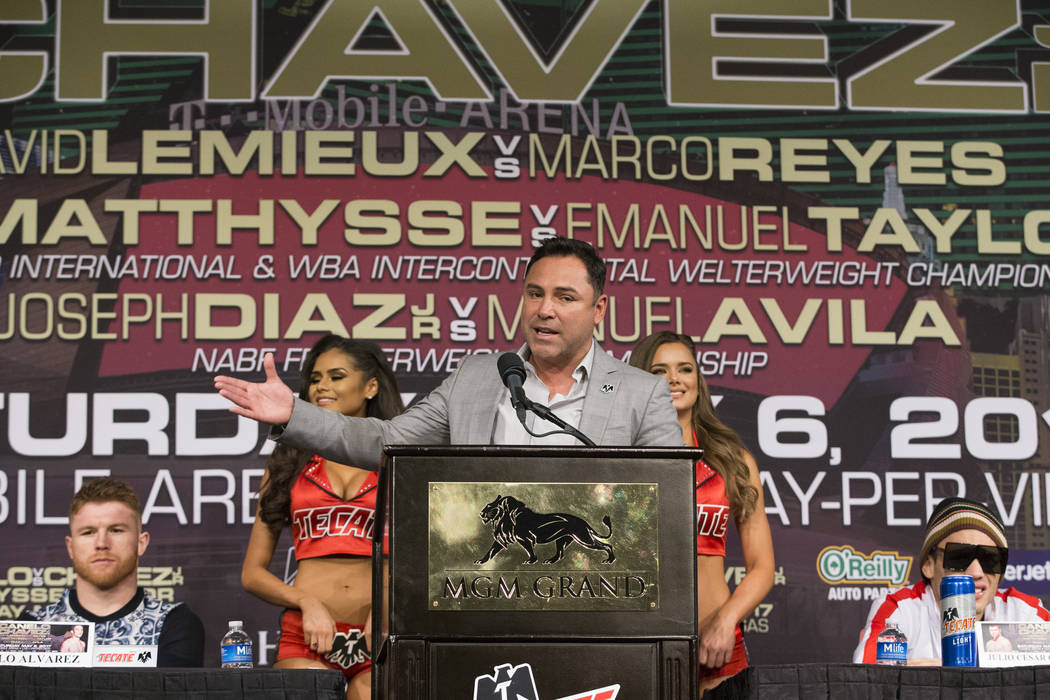 "Golden Boy Promotions CEO Oscar De La Hoya, center, speaks during the final boxing press conference before the fight between Saul Canelo ""Canelo"" Alvarez, left, and Julio Cesar C ..."