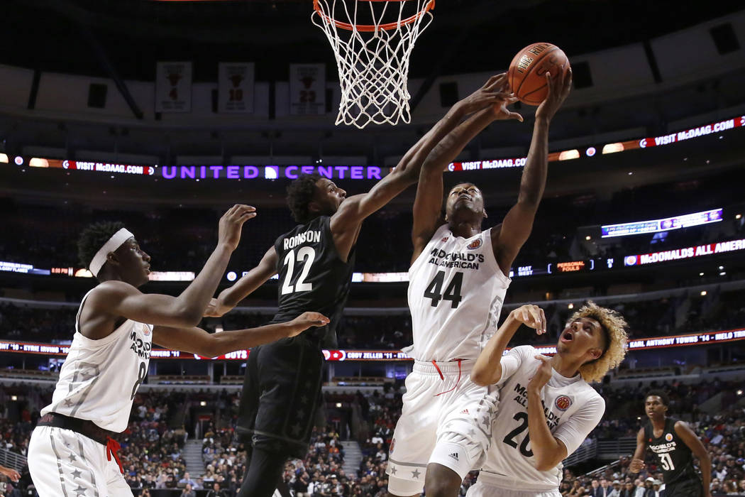 """Big East's Mitchell Robinson (22) blocks the shot of Big West's Brandon L. McCoy (44) as Jaren Jackson Jr., left, and Brian """"Tugs"""" Bowen II, watch during the second half of the M ..."""