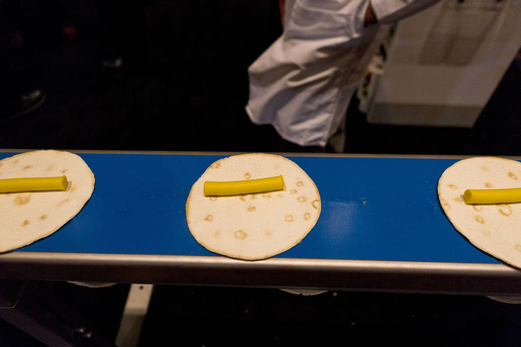 The VEMAG Robot 500 dough portioner quickly forms modeling compound as an example of different foods that can rapidly be prepared during the Tortilla Industry Association Annual Convention at Pari ...