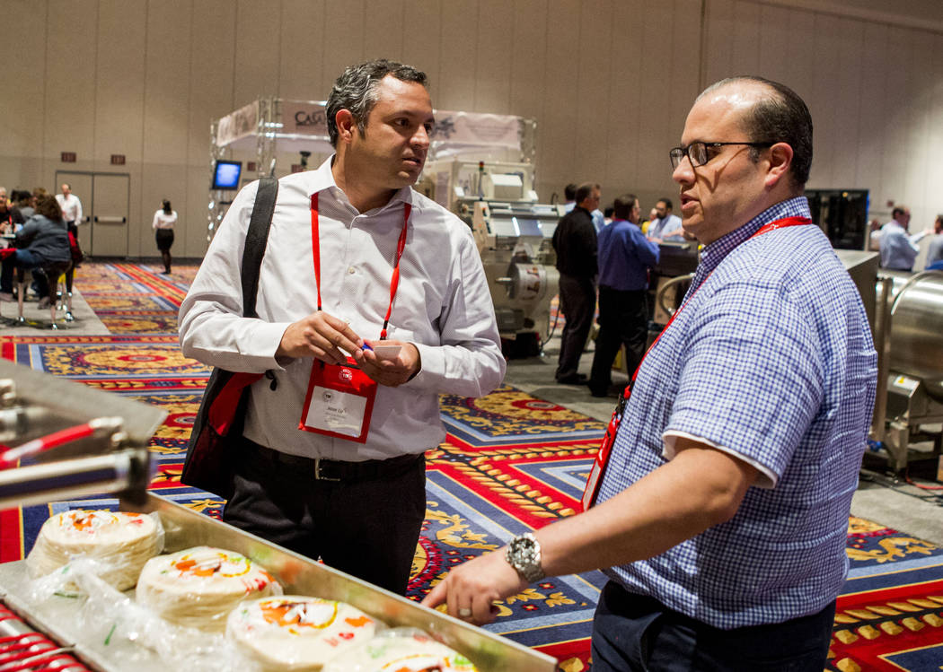 Jose Luis Heredia Villagomez, left, owner of La Regia Tortilla Factory, and employee Jorge Contreras explore different machine options for quick tortilla making during the Tortilla Industry Associ ...