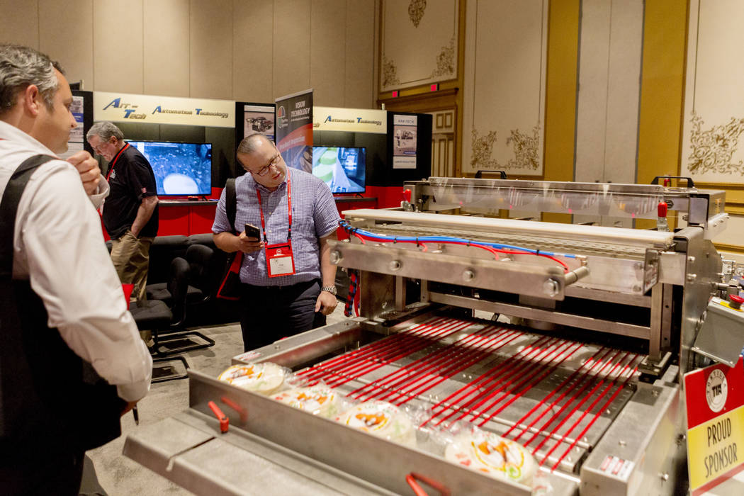 Jose Luis Heredia Villagomez, left, owner of La Regia Tortilla Factory, and employee Jorge Contreras, looks at an Arr-Tech machine during the Tortilla Industry Association Annual Convention at Par ...
