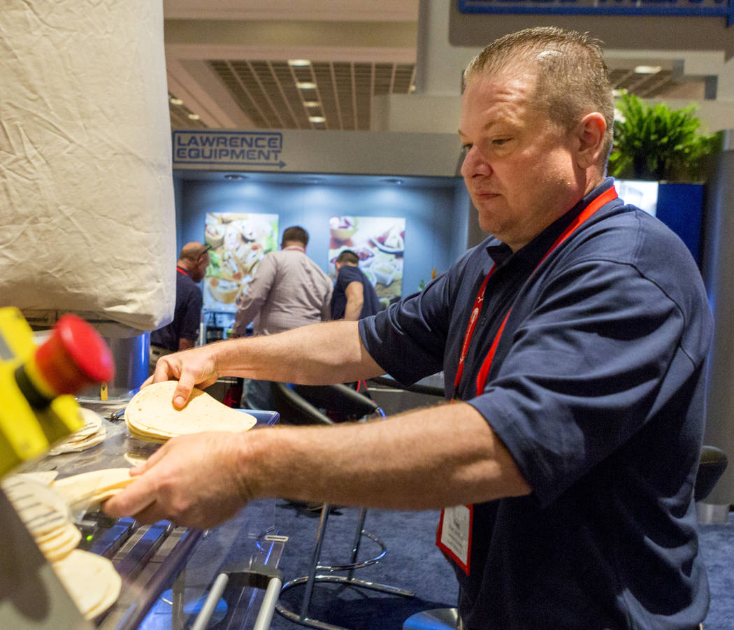 Lawrence Equipment technician Fred Uhrmann demonstrates one of their convert belt machines for packaging during the Tortilla Industry Association Annual Convention at Paris Las Vegas, May 1, 2017. ...