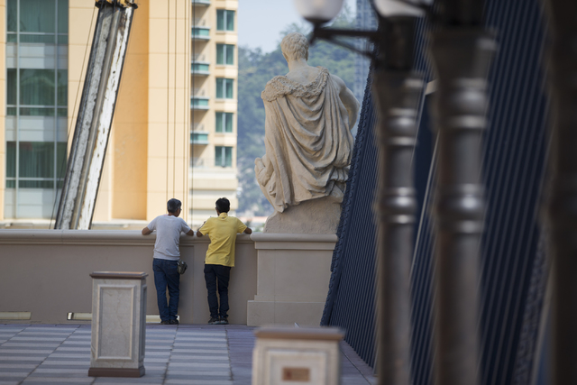 Two men stand outside of the Parisian Macao hotel-casino on Wednesday, Sept. 14, 2016, in Macau. Erik Verduzco/Las Vegas Review-Journal Follow @Erik_Verduzco