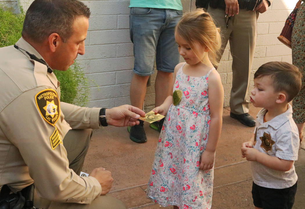 Sgt. Steve Armbruster, left, gives Rowan, 4, and Keegan, 2, police badge stickers during Coffee with a Cop at the Donut Bar in downtown Las Vegas, Thursday, May 4, 2017. (Gabriella Benavidez/Las V ...