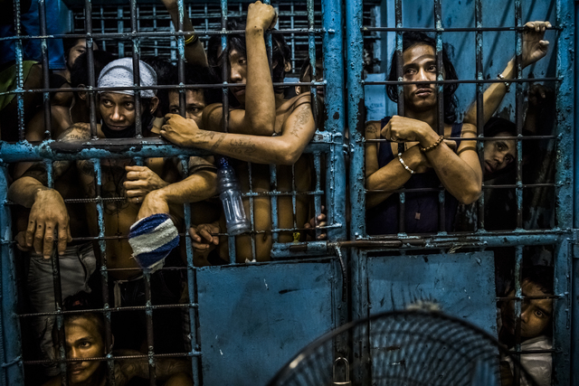 Inmates watch as drug suspects are processed inside a police station in Manila, Philippines. President Rodrigo Duterte began his anti-drug campaign when he took office on June 30, 2016. Since then ...