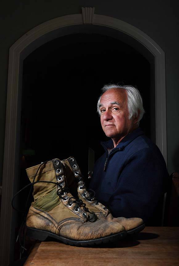 George Chaconas sits next to boots he wore in Vietnam at his home in Washington. (Matt McLain/The Washington Post)