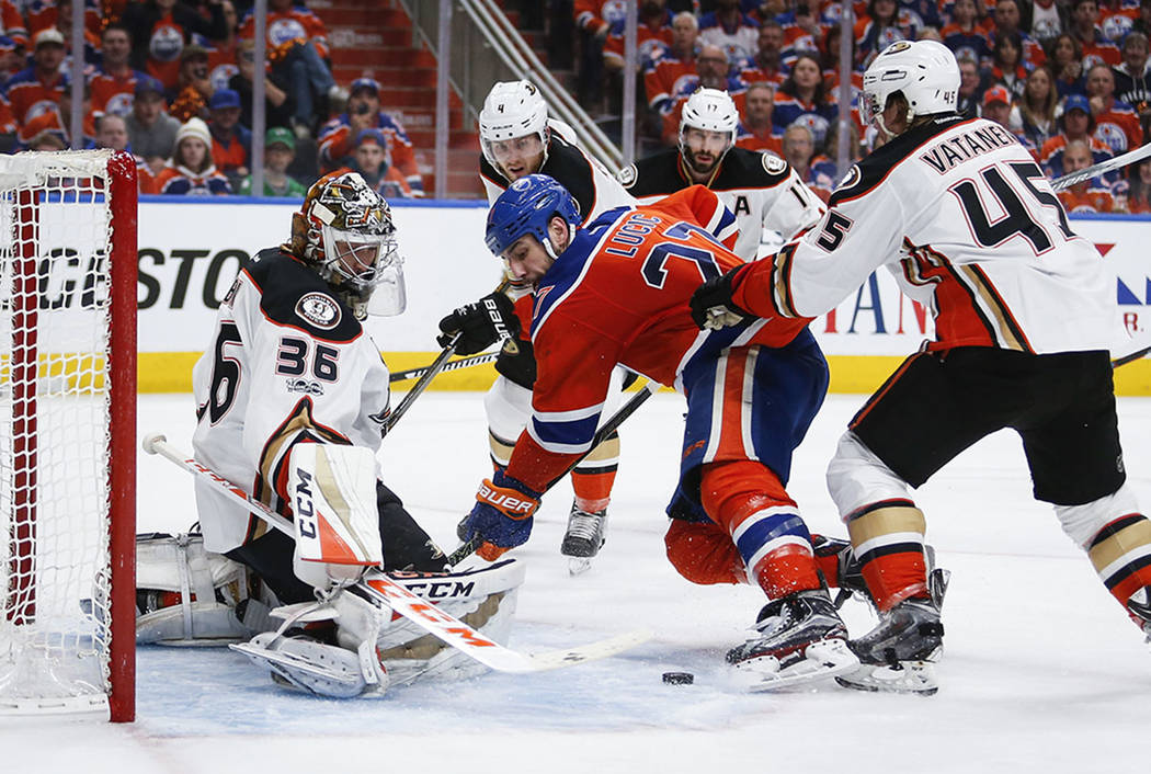 Anaheim Ducks goalie John Gibson, left, blocks the net on Edmonton Oilers' Milan Lucic, center, during the second period in Game 3 of a second-round NHL hockey Stanley Cup playoff series in Edmont ...