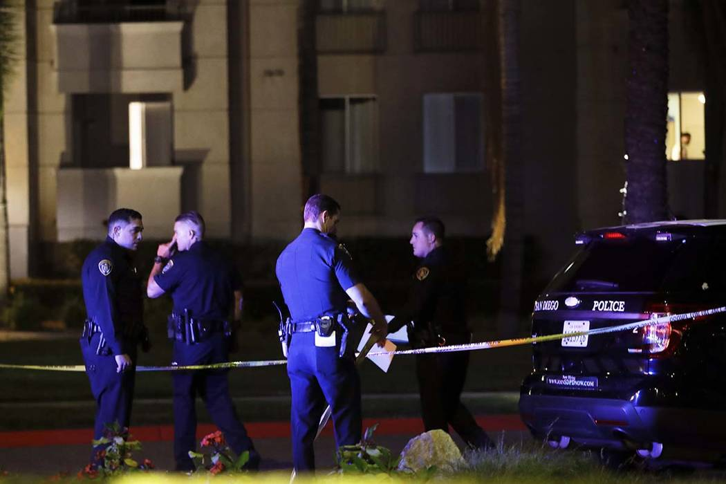 San Diego police officers stand in front of a cordoned off La Jolla apartment after a shooting Sunday, April 30, 2017, in San Diego. Police shot and killed a 49-year-old man suspected of shooting  ...