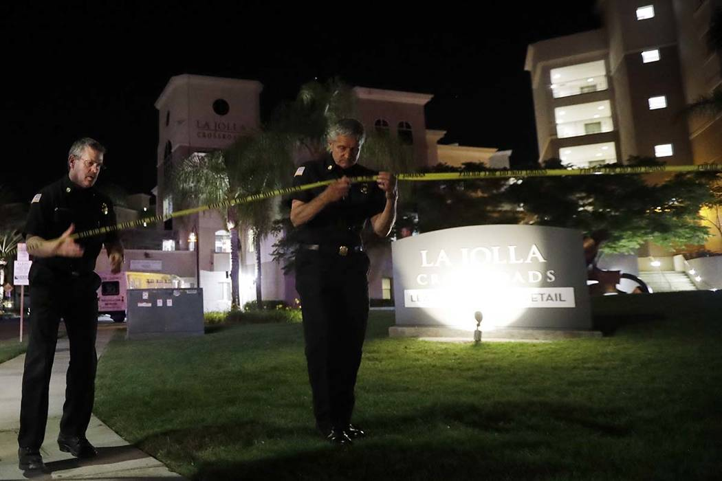 San Diego police officers work at a cordoned off La Jolla apartment after a shooting Sunday, April 30, 2017, in San Diego. Police shot and killed a 49-year-old man suspected of shooting seven peop ...