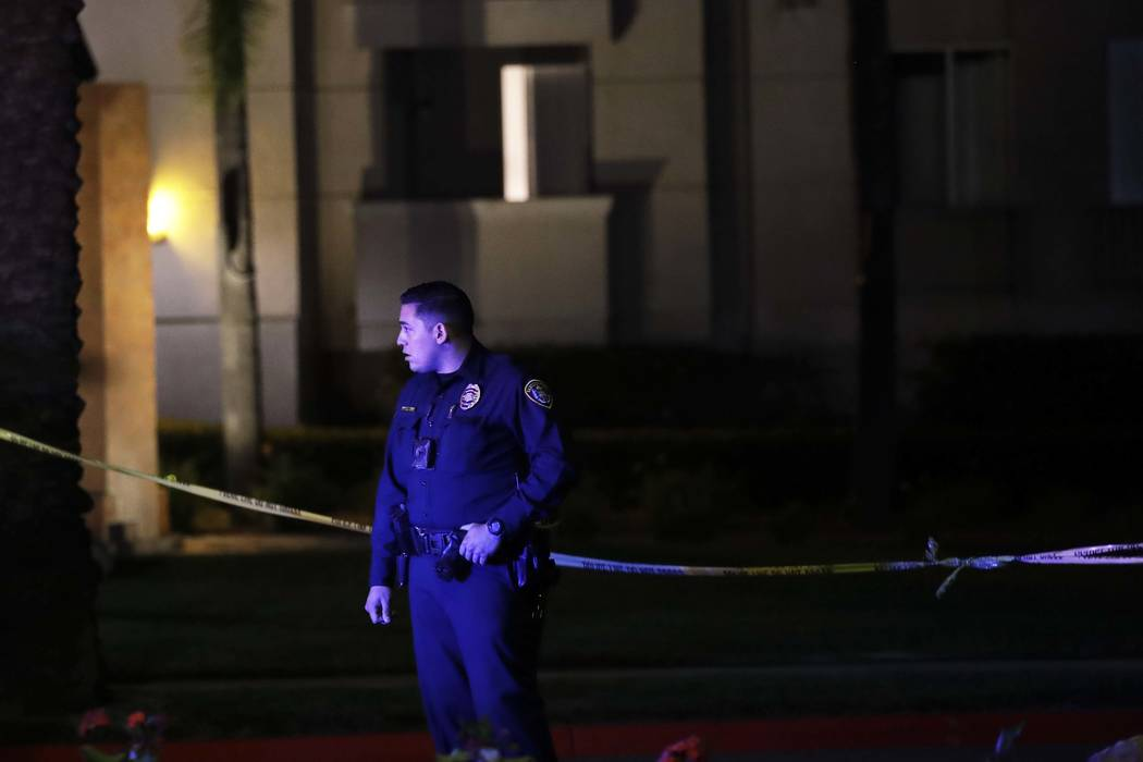 A San Diego police officer stand guard in front of a cordoned off La Jolla apartment after a shooting Sunday, April 30, 2017, in San Diego. Police shot and killed a 49-year-old man suspected of sh ...