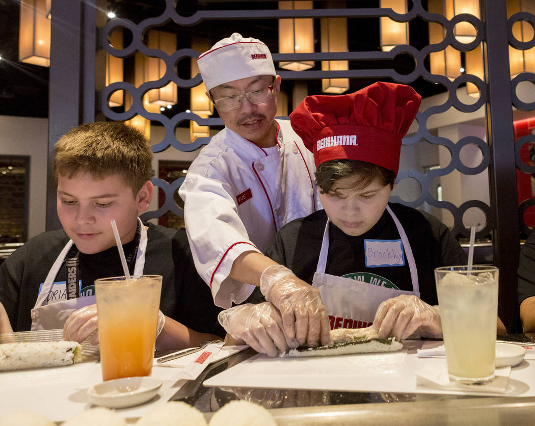 Benihana head sushi chef Vue Vang demonstrates how to roll sushi to Harney Middle School students Adrian Ceja, 12, left, and Brooklyn Madera, 12, at Benihana inside Fashion Show mall in Las Vegas  ...