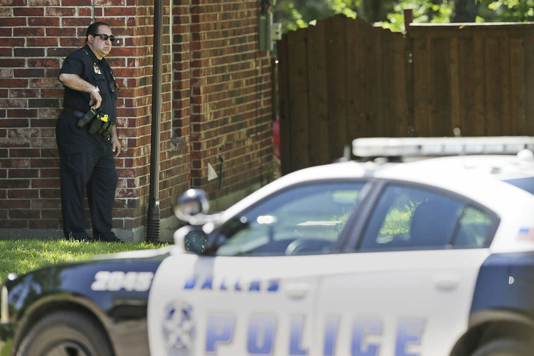 A Dallas Police officer takes a position a block away from a shooting in Dallas, Monday, May 1, 2017. Authorities said a Dallas paramedic has been shot while responding to a shooting call.  (LM Ot ...