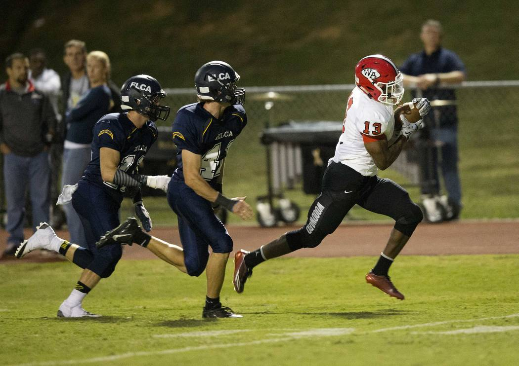 In this Sept. 26, 2014, file photo, Woodward Academy running back Elijah Holyfield runs for a touchdown after catching a pass against Eagle's Landing Christian Academy in the first half of a high  ...