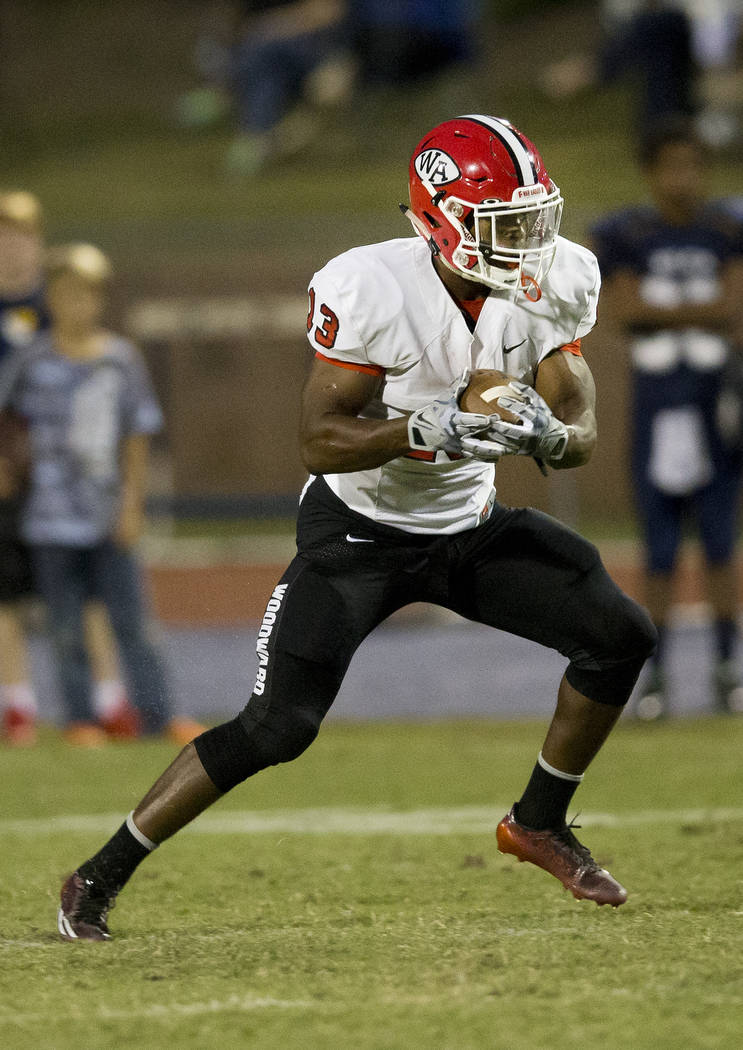 In this Friday, Sept. 26, 2014 photo, Woodward Academy running back Elijah Holyfield, son of five-time boxing champion Evander Holyfield, runs against Eagle's Landing Christian in the first half o ...