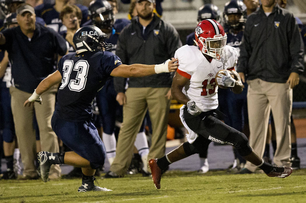 In this Friday, Sept. 26, 2014 photo, Woodward Academy running back Elijah Holyfield, son of five-time boxing champion Evander Holyfield runs for a touchdown after catching a pass against Eagle's  ...