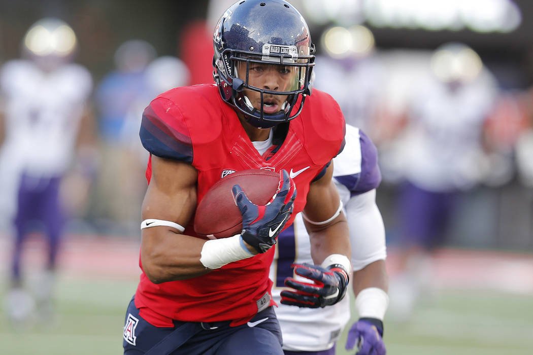 Arizona running back Trey Griffey (5) makes the catch in front of Washington defensive back John Ross (1) during the second half of an NCAA college football game, Saturday, Nov. 15, 2014, in Tucso ...