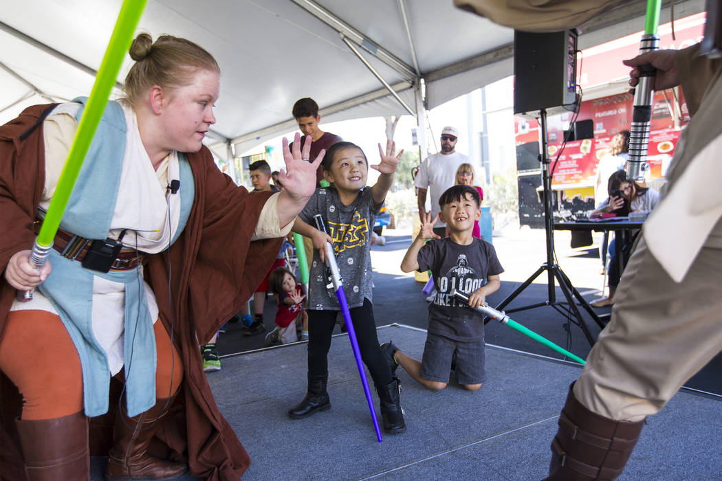 """Amanda Bond of the Nar Shaddaa Temple Saber Guild, left, teaches Tenley Chow, 4, center, and Jace Chow, 5, during the """"May Science Be With You"""" event, held by the National Atomic Testing Museum an ..."""