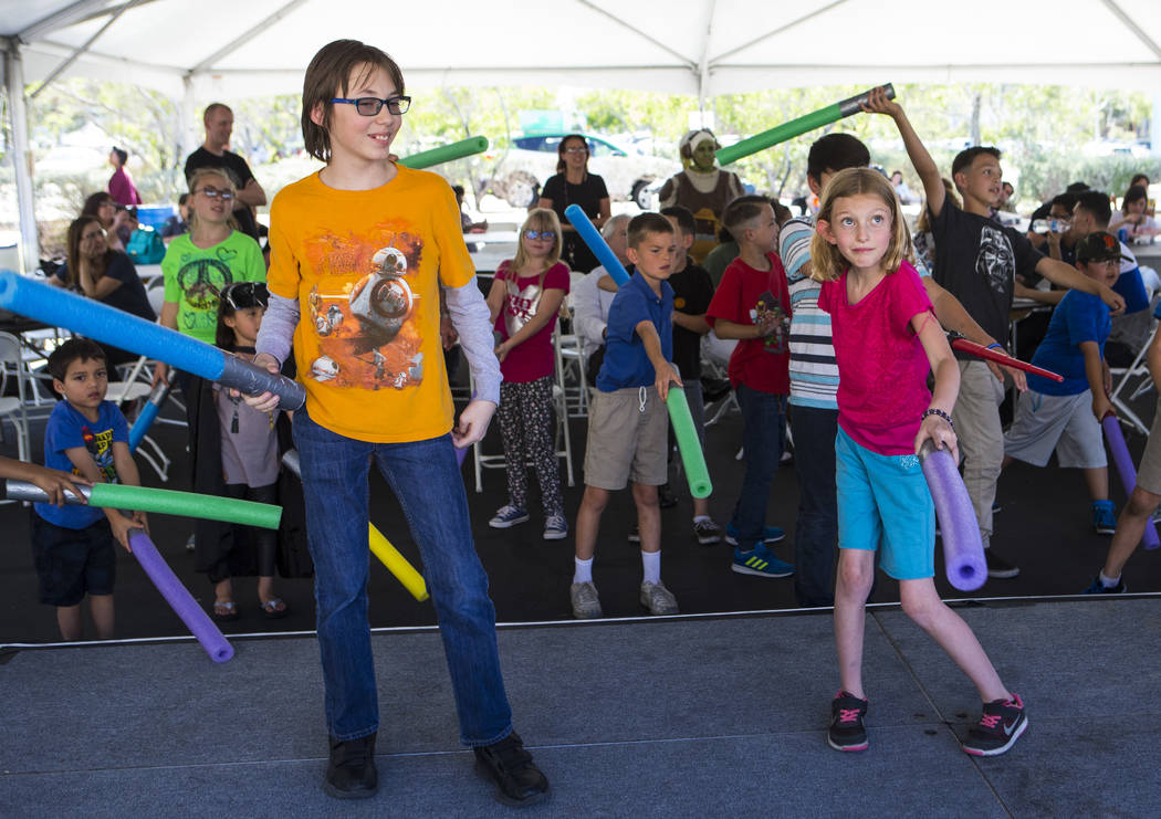 """Steven Davis, 11, left, and Lorraine Deane, 9, participate in lightsaber training during the """"May Science Be With You"""" event, held by the National Atomic Testing Museum and the D ..."""