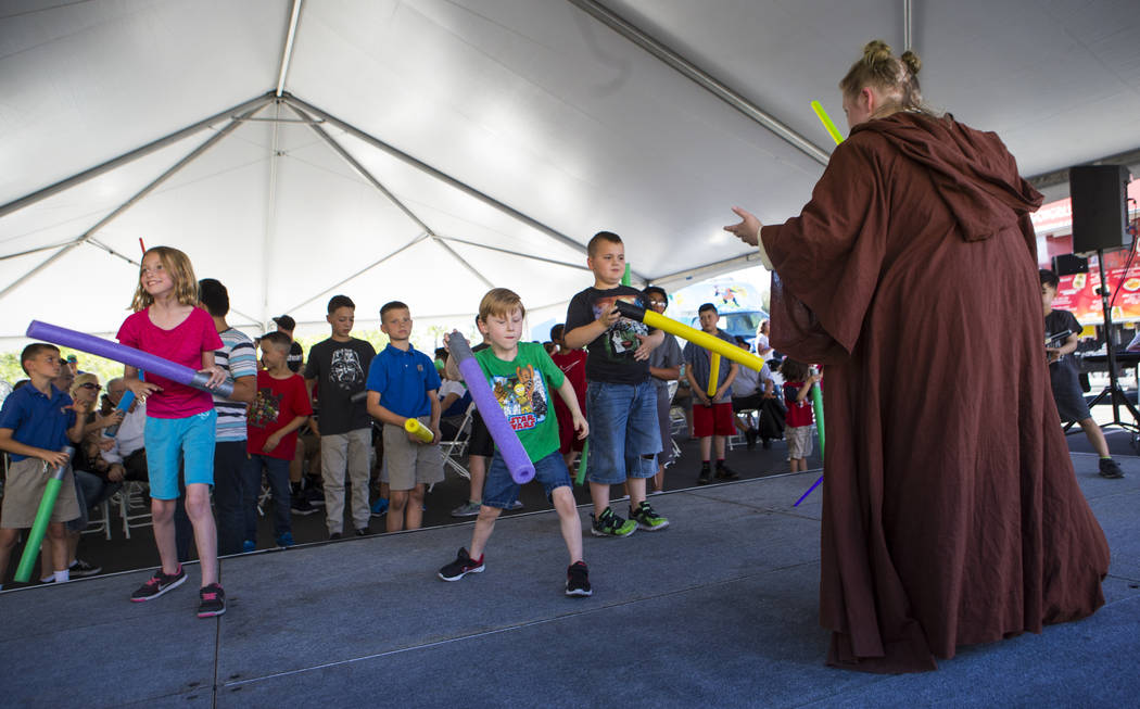"""Amanda Bond of the Nar Shaddaa Temple Saber Guild teaches children how to use a lightsaber during the """"May Science Be With You"""" event, held by the National Atomic Testing Museum  ..."""