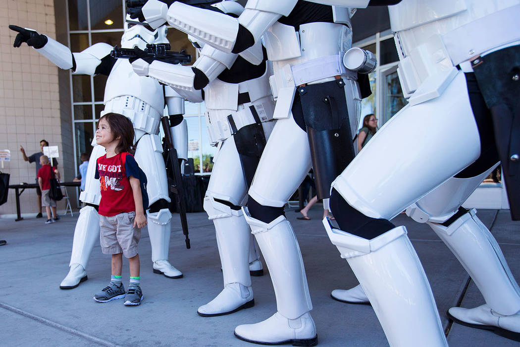 """Ryder Caldera, 3, poses with members of the 501st Legion during the """"May Science Be With You"""" event, held by the National Atomic Testing Museum and the Desert Research Institute, ..."""