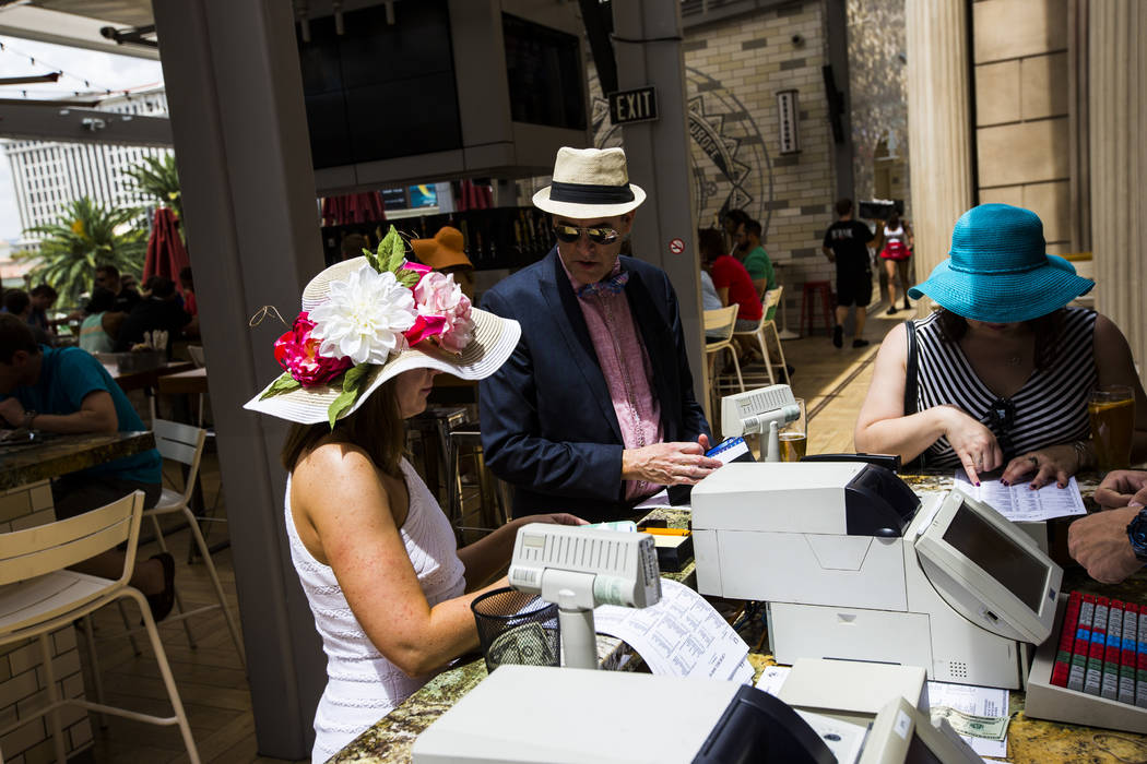 Katie and Joe Komer, left, with Tara Bird, right, place bets during a Kentucky Derby viewing party at Beer Park at the Paris hotel-casino in Las Vegas on Saturday, May 6, 2017. Chase Stevens Las V ...