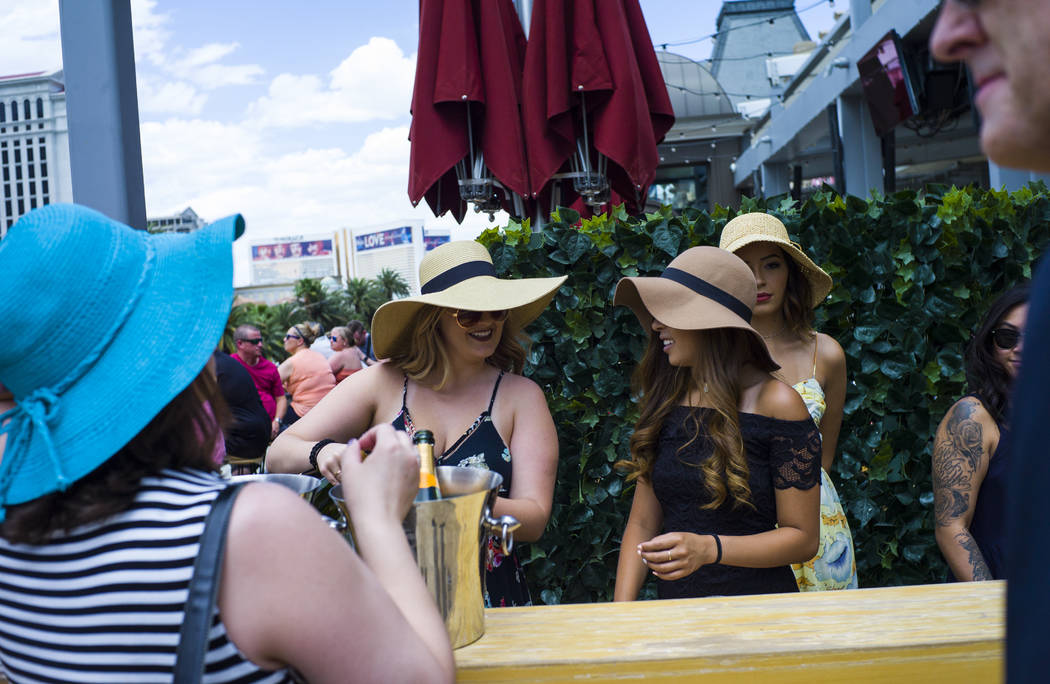 Manager Rachel Headley, left, pours champagne for arriving guests at Beer Park at the Paris hotel-casino for a Kentucky Derby viewing party in Las Vegas on Saturday, May 6, 2017. Chase Stevens Las ...