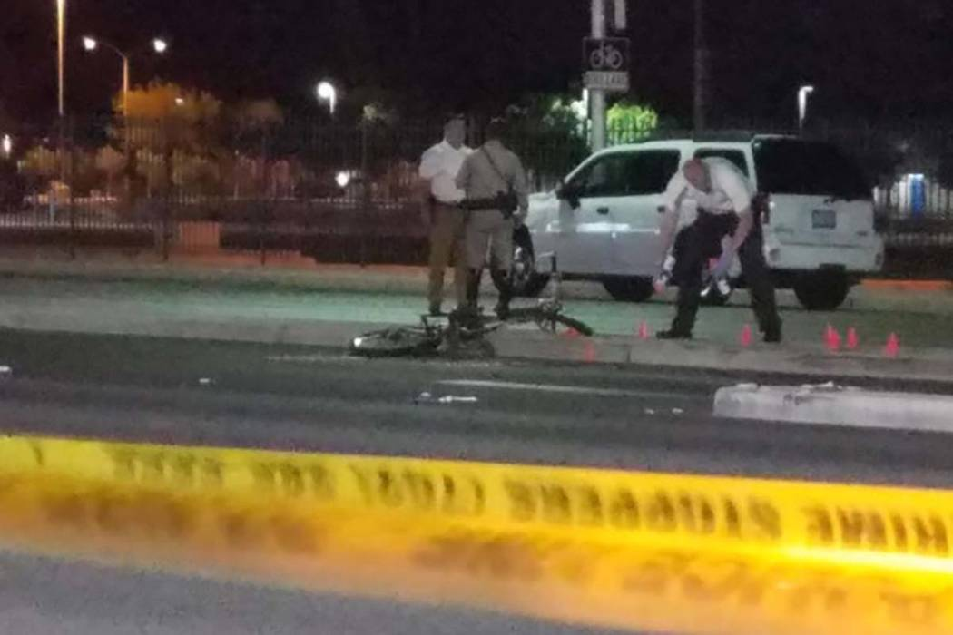 Las Vegas police investigate the scene where an SUV and a bicyclist collided Monday night on Decatur Boulevard just south of Vegas Drive. The bicyclist was pronounced dead at the scene. (Mike Shor ...