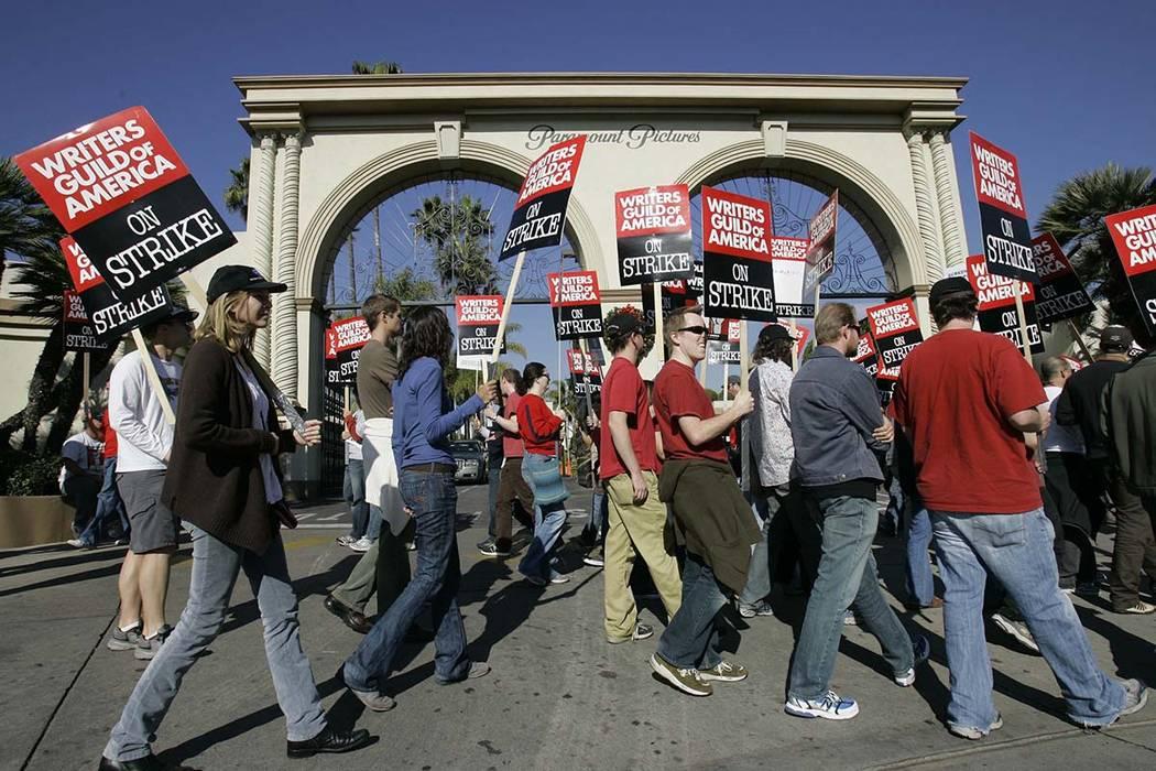 FILE - In this Dec. 13, 2007, file photo, striking writers walk the picket line outside Paramount Studiosin Los Angeles. (Nick Ut/AP)