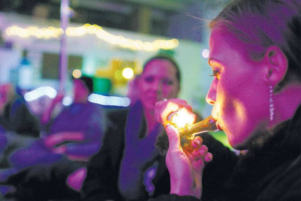 Rachel Schaefer of Denver smokes marijuana Dec. 31, 2012, on the official opening night of Club 64, a marijuana-specific social club, where a New Year's Eve party was held in Denver. Despite passi ...
