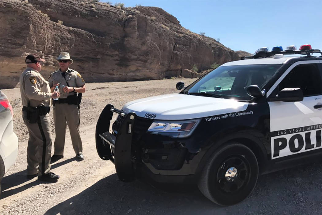Two Metro officers block an entrance to Eagle Wash Road, the direction where remains were found encased in cement near Lake Mead National Recreation Area on Tuesday, May 2, 2017. (Bridget Bennett/ ...