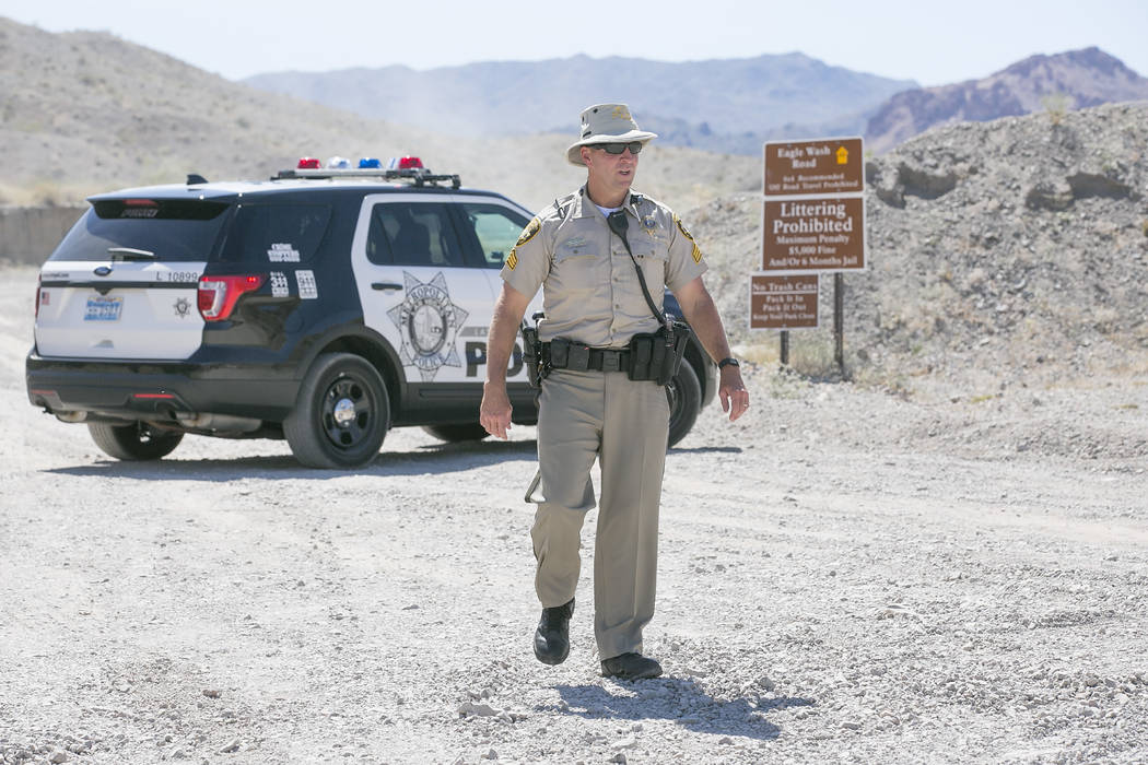 Las Vegas Metropolitan Police Srgnt. Eugene Gallagher stand guard at an entrance to Eagle Wash Road, which leads to the crime scene, at Lake Mead National Recreation Area on Tuesday, May 2, 2017.  ...