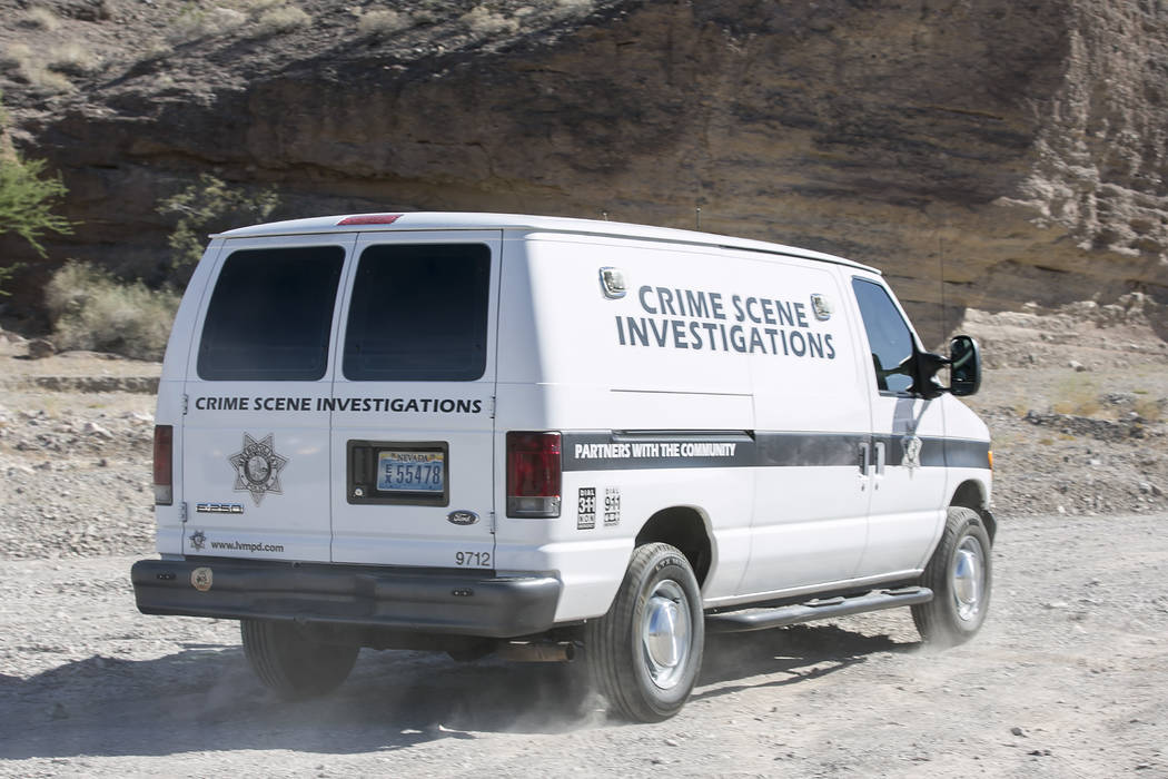 A Las Vegas Metropolitan Crime Scene Investigations van arrives at an entrance to Eagle Wash Road, that leads to the crime scene, at Lake Mead National Recreation Area on Tuesday, May 2, 2017. Bri ...