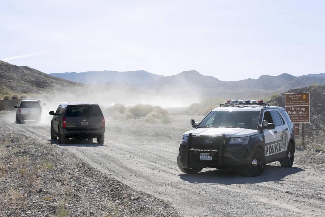 A Las Vegas Metropolitan Crime Scene Investigations van and other emergency vehicles make their way up Eagle Wash Road, which leads to the crime scene, at Lake Mead National Recreation Area on Tue ...