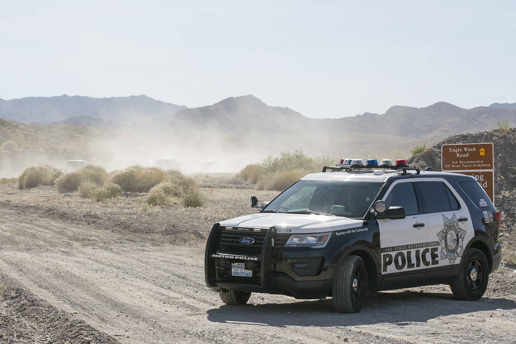 A Las Vegas Metropolitan Police officer block an entrance as emergency vehicles make their way up Eagle Wash Road, which leads to the crime scene, at Lake Mead National Recreation Area on Tuesday, ...