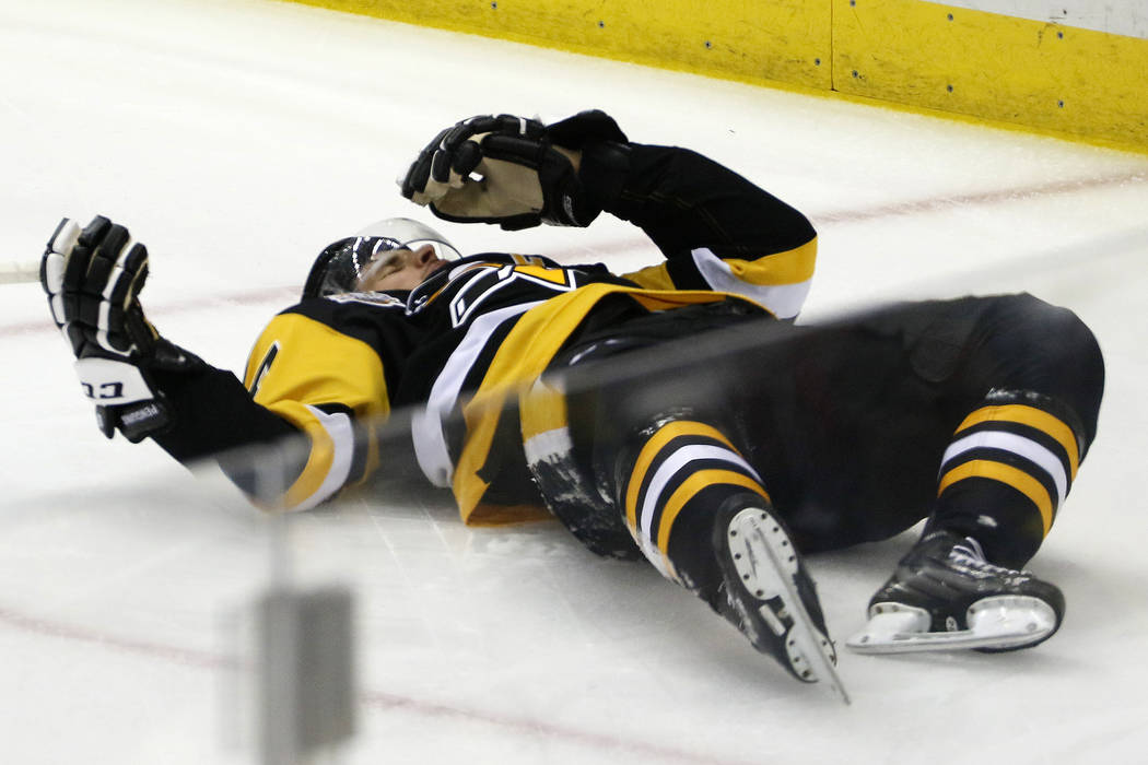 Pittsburgh Penguins' Sidney Crosby (87) lies on the ice after taking a hit from Washington Capitals' Matt Niskanen during the first period of Game 3 in an NHL Stanley Cup Eastern Conference semifi ...