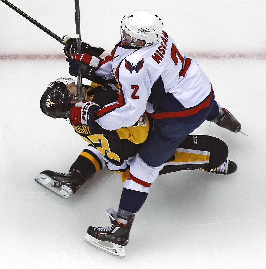 Pittsburgh Penguins' Sidney Crosby (87) takes a hit from Washington Capitals' Matt Niskanen during the first period of Game 3 in an NHL Stanley Cup Eastern Conference semifinal hockey game against ...