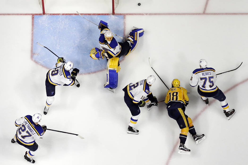 St. Louis Blues goalie Jake Allen, top, reaches for a shot as several teammates and Nashville Predators right wing James Neal (18) watch for the rebound during the third period in Game 4 of a seco ...
